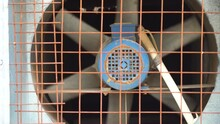 Industrial Fan Rotating With A Draft Of Wind With A Motor Attached With A Checkerboard Cage In Front. Shows The Ventilation System Of A Residential Office Lift Used To Cool And Remove Any
