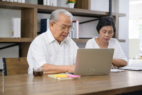 Carta da parati A happy senior Asian couple is spending time on surfing  the internet and talking with family on webcam,  retirement concept
