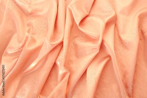 Fototapeta beautiful silk fabric of delicate doggie color, light orange, draped with small