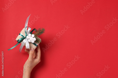 Slika na platnu Woman holding giftbox of kraft paper with ribbons on red background