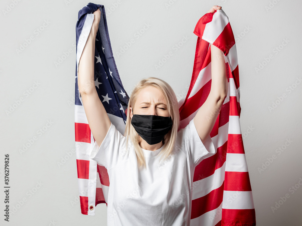 Fototapeta Blonde girl in face mask with USA flag on white background