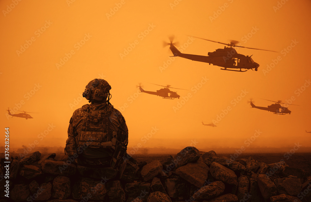Fototapeta Military helicopter and forces in desert and one soldier sits and looks at the battle field