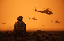 Military Helicopter And Forces In Desert And One Soldier Sits And Looks At The Battle Field