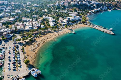 ELOUNDA, CRETE, GREECE - 27 AUGUST 2020: Aerial view of the public beach in the popular Greek tourist town of Elounda on the island of Crete