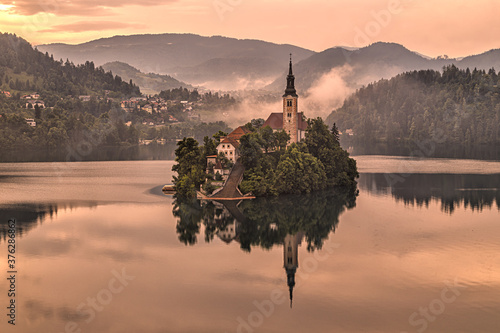 Fotografie, Obraz Lake Bled after colorful sunset, orange sky reflected in the water, Bled island with small pilgrimage Church, mountains in the background, Slovenia, Europe
