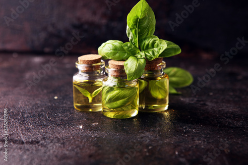 Tableau sur Toile A transparent glass bottle of basil essential oil with fresh basil leaves on rus