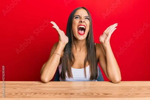 Young hispanic woman wearing casual clothes sitting on the table celebrating mad and crazy for success with arms raised and closed eyes screaming excited Fototapete