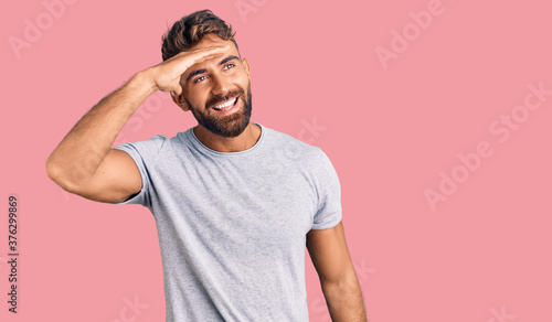 Young hispanic man wearing casual clothes very happy and smiling looking far away with hand over head Billede på lærred