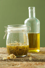 Herbal Infused Oil. Yellow Immortelle Flowers And Cold Pressed Olive Oil In A Glass Jar. Process Of Maceration.