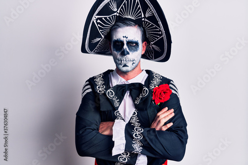 Cuadros en Lienzo Young man wearing mexican day of the dead costume over white skeptic and nervous, disapproving expression on face with crossed arms