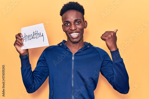 Photo Young african american man holding healthy hashtag paper pointing thumb up to th