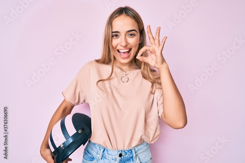 Young beautiful blonde woman holding motorcycle helmet doing ok sign with fingers, smiling friendly gesturing excellent symbol
