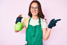 Young Beautiful Chinese Girl Wearing Apron Holding Sprayer Smiling Happy Pointing With Hand And Finger To The Side
