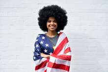 Happy Young African American Woman With Afro Hair Standing On White Background Wrapped In USA Flag Looking At Camera Outdoor. Independent Confident Smiling Mixed Race Lady Headshot Portrait.