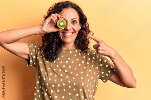 Foto Middle age beautiful woman holding kiwi over eye smiling happy pointing with han