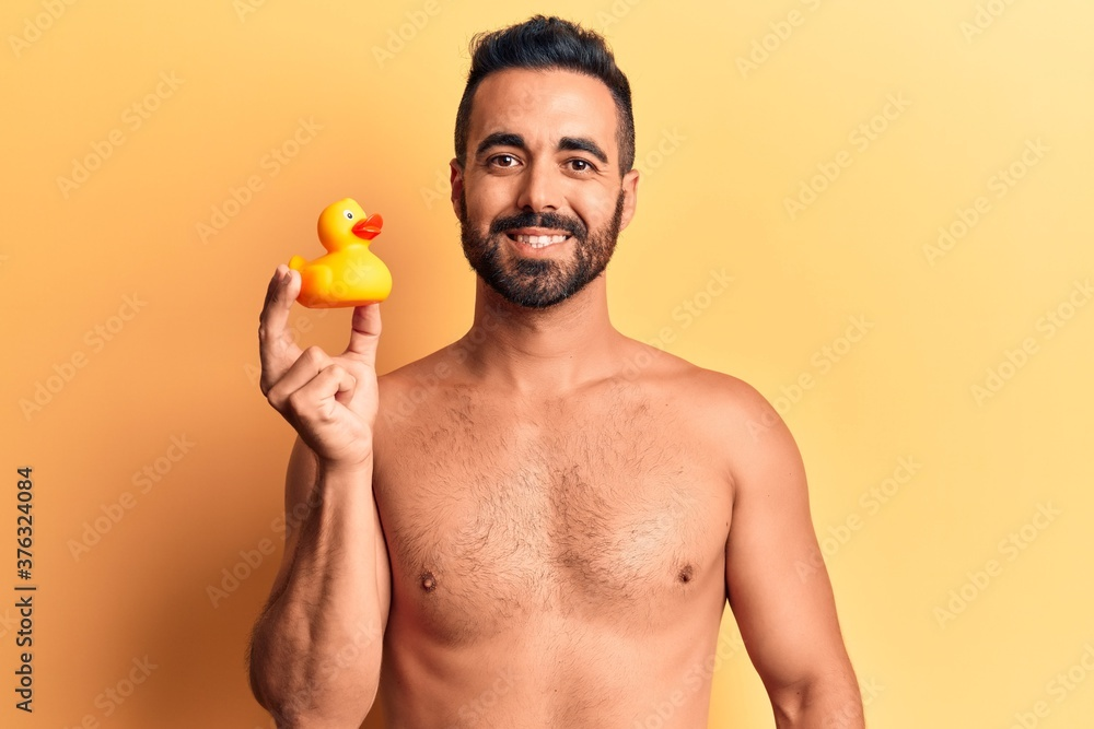 Fototapeta Young hispanic man standing shirtless holding duck toy looking positive and happy standing and smiling with a confident smile showing teeth