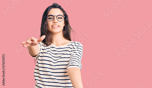 Obraz na plátně Brunette teenager girl wearing casual clothes and glasses looking at the camera smiling with open arms for hug