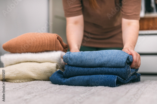 Fotografija Woman folds in a stack of sweaters and jeans