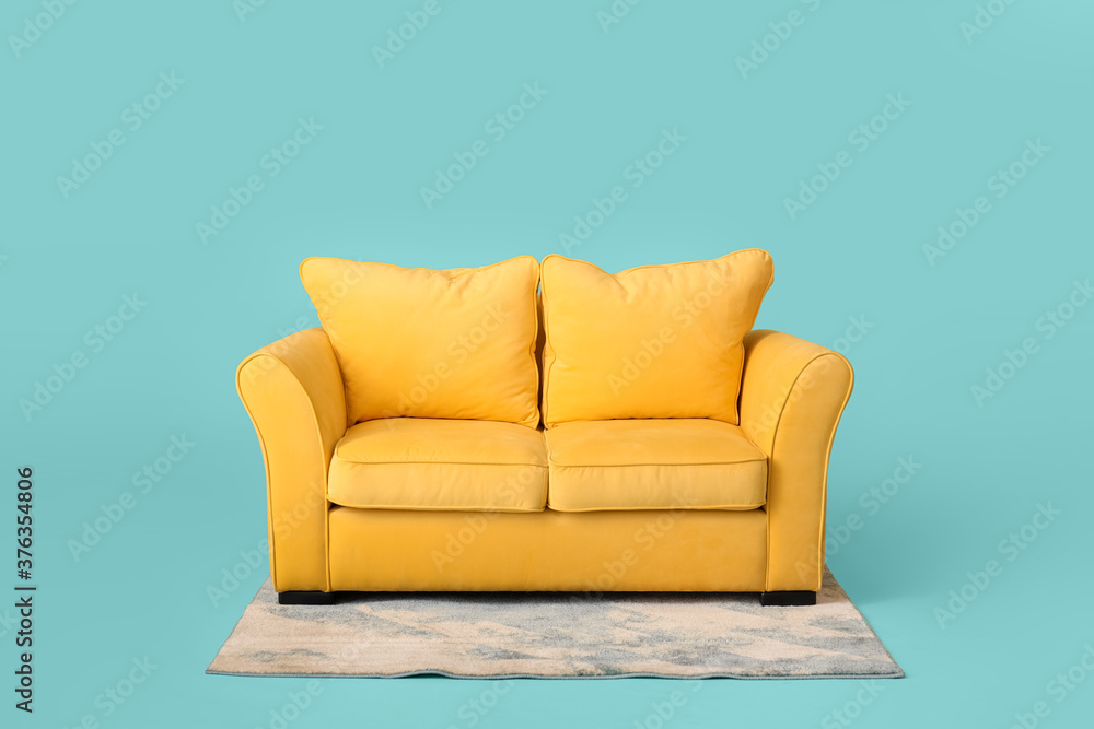 Fototapeta Stylish sofa and carpet on color background