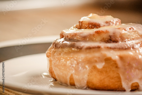 Fototapeta Delicious hot cinnamon roll with icing