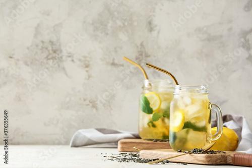Mason jars of tasty cold ice tea on table