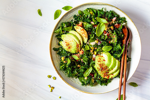 Leinwand Poster Healthy salad with kale, quinoa, nuts and avocado in white bowl, top view
