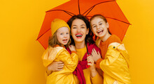 Family With Umbrella On Colored Background.