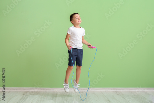 Fényképezés Cute little boy jumping rope near color wall