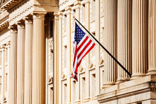 US Flag Over Classical Government Building With Columns In Washington, DC