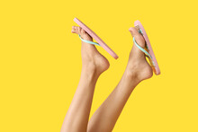 Legs Of Young Woman In Flip-flops On Color Background