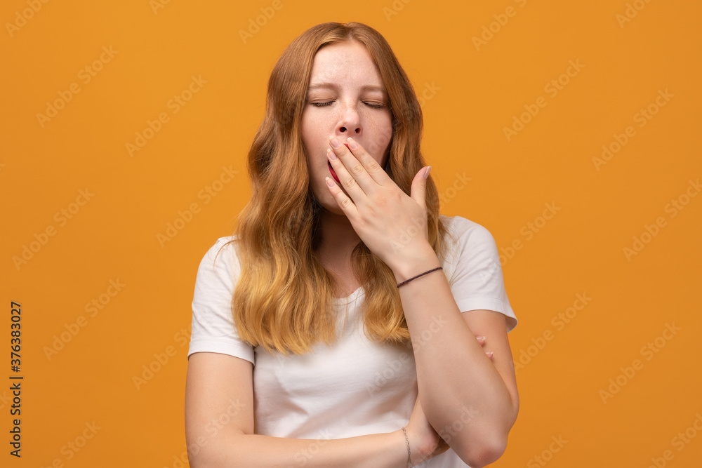 Fototapeta Young beautiful woman with wavy redhead bored yawning tired covering mouth with hand. Restless and sleepiness
