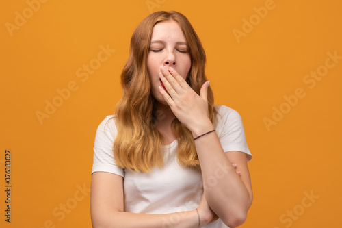 Obraz Young beautiful woman with wavy redhead bored yawning tired covering mouth with hand. Restless and sleepiness - fototapety do salonu