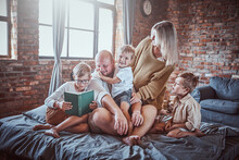 Husband And Wife With Their Children Teaching Them To Read A Book And Having A Good Time In Playing And Living Room.