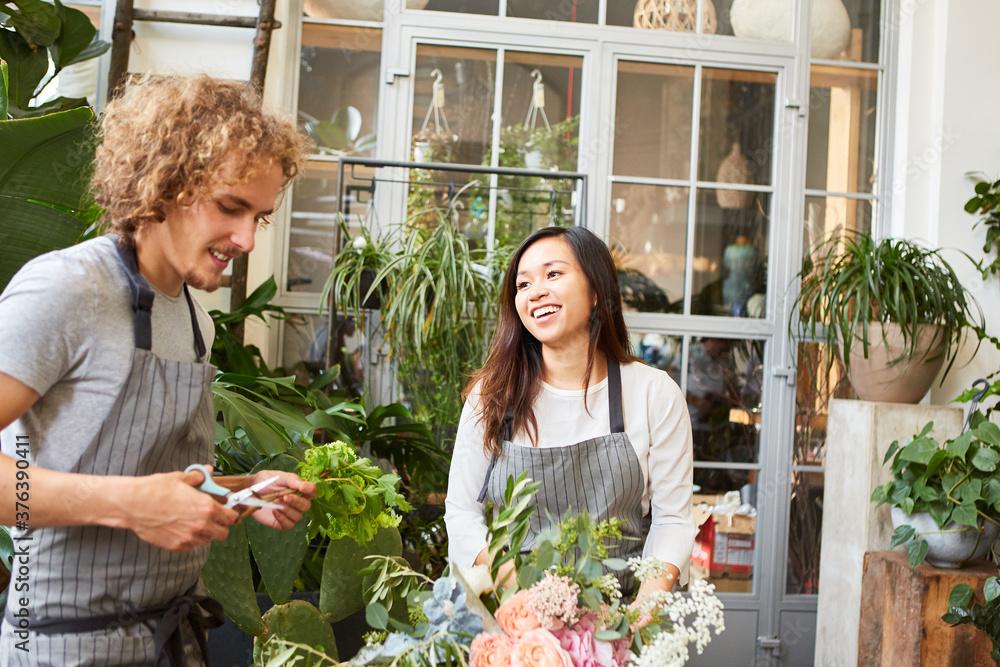 Fototapeta Young florist and colleague tie bouquet