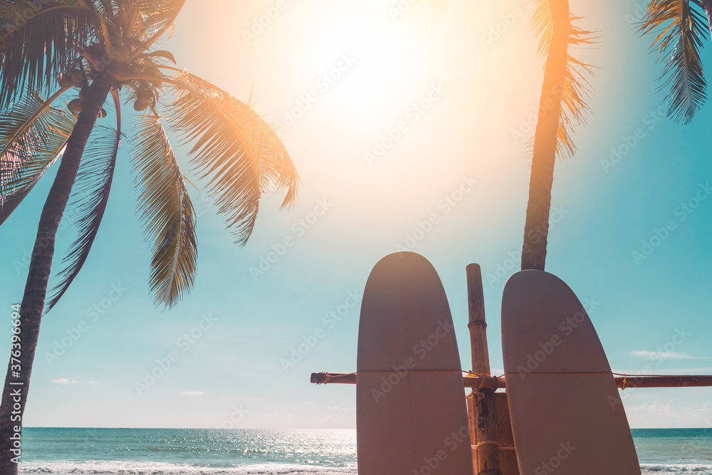 Fototapeta Surfboard and palm tree on sunset sky abstract background. Summer vacation and sport extreme concept.