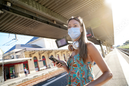 Obraz na plátne Young woman waiting for train on railway platform, wearing face mask