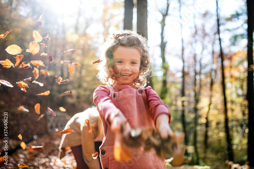 Fotografía Small girl with mother on a walk in autumn forest, throwing leaves