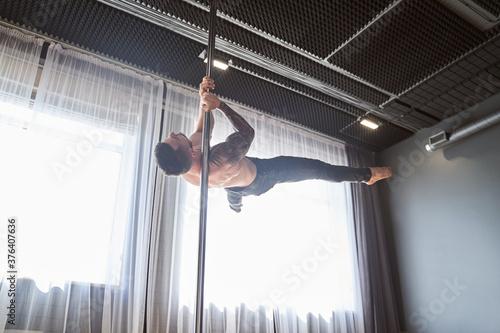 Fotografia Young strong pole dancer man in black pants on pylon