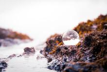 Crystal Ball In The Ocean And Beach Rocks