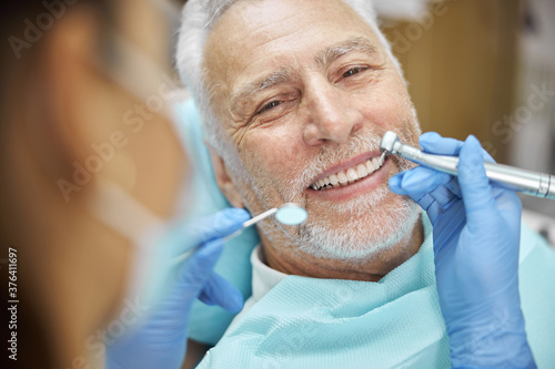 Fotografía Mirthful senior citizen smiling during a dental treatment