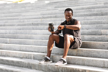 African Athete Guy Checking Fitness Tracker After Training Outdoors, Sitting On Steps