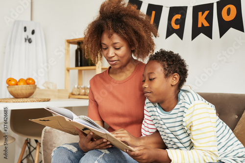 Fotografija Beautiful African American woman sitting on sofa in living room with her preteen