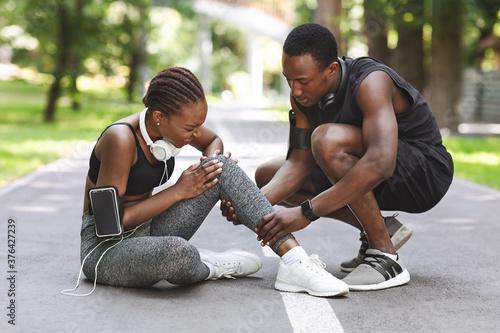 Fototapeta Sport Injury. Woman Suffering From Knee Trauma While Jogging With Boyfriend Outdoors obraz