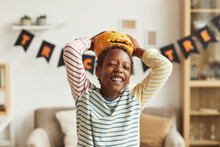 Playful African American Boy Having Fun With Jack O' Lantern Pumpkin Putting It On His Head, Medium Portrait Shot
