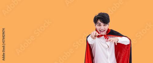 Valokuvatapetti Asian man wearing Halloween costume as vampire Dracula on orange background, hol