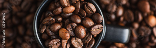 Fotografia top view of fresh roasted coffee beans in cup, panoramic shot