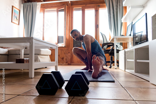 Young caucasian european spanish man training at home with dumbbells and mat - Stay at home fitness wourkout equipment