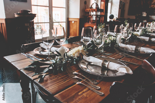 Fotografie, Obraz Wedding banquet, serving wooden table with silver plates and decorated with flow