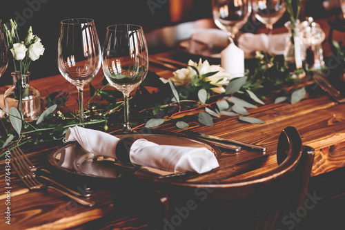 Wedding banquet, serving wooden table with silver plates and decorated with flow Canvas Print