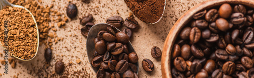 Foto top view of ground, instant coffee and beans in spoons near wooden bowl on beige